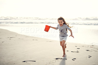 Buy stock photo Shot of a little girl holding a bucket while playing on the beach