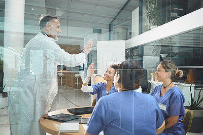 Buy stock photo Shot of doctors giving each other a high five during a meeting in a hospital