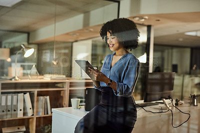 Buy stock photo Shot of a young businesswoman using a digital tablet during a late night in a modern office