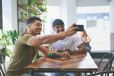 Buy stock photo Cropped shot of two handsome friends sitting together and using a cellphone to take a selfie in a coffeeshop