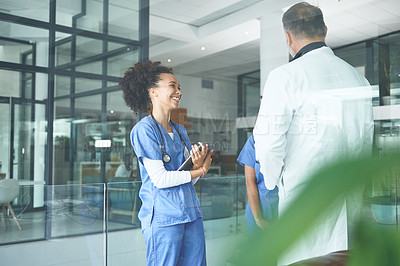 Buy stock photo Cropped shot of an attractive young nurse standing with coworkers and having a discussion in the clinic