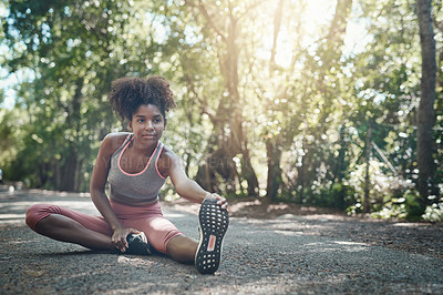 Buy stock photo Shot of a young woman stretching before a workout