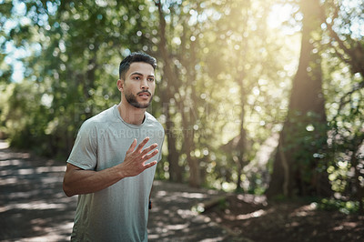 Buy stock photo Shot of a young man running in a forest