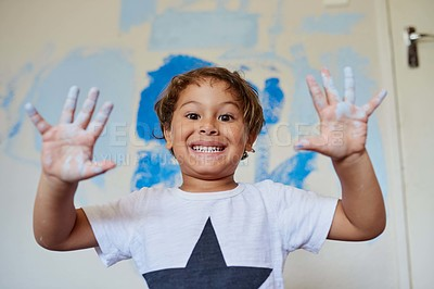 Buy stock photo Shot of a little boy showing off his dirty hands while painting a room blue