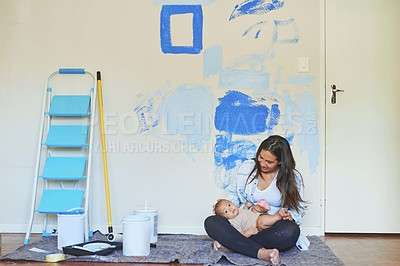 Buy stock photo Shot of a woman sitting with a baby in a unfinished nursery
