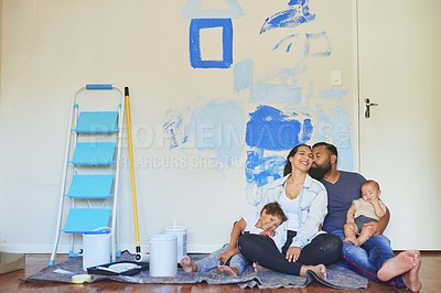 Buy stock photo Shot of a couple sitting at home with their kids while busy painting a room