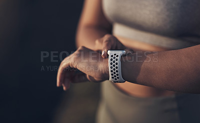 Buy stock photo Shot of a woman checking her smartwatch while out for a workout