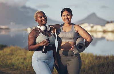 Buy stock photo Shot of two young women holding a water bottle and yoga mat while standing outside