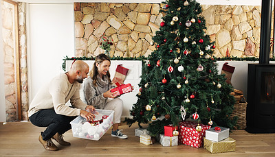 Buy stock photo Shot of a happy couple decorating their Christmas tree and laying out presents at home