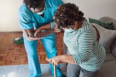 Buy stock photo Shot of a young male nurse helping an elderly patient stand