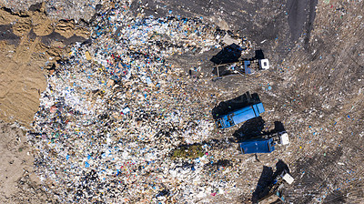 Buy stock photo High angle shot of garbage trucks at a landfill