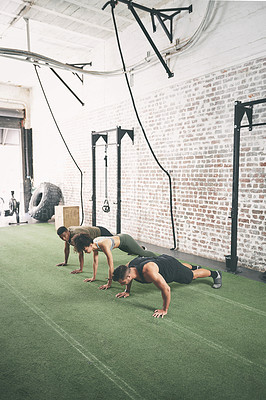 Buy stock photo Shot of a fitness group doing push-ups at the gym