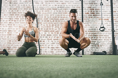 Buy stock photo Shot of two sporty young people dusting off their hands while working out at the gym