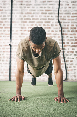 Buy stock photo Shot of a sporty young man doing pushups at the gym