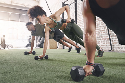 Buy stock photo Shot of a fitness group using dumbbells while doing push-ups at the gym