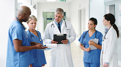 Buy stock photo Shot of a male nurse discussing his notes with his diverse team of medical colleagues