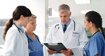 Buy stock photo Shot of a senior male doctor discussing his notes with his female colleagues in the hallway of the hospital