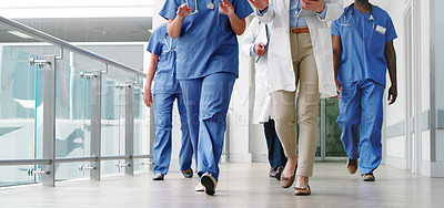 Buy stock photo Cropped shot of a diverse group of uunrecognizable medical practitioners walking in the hallway of the hospital