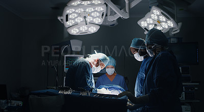 Buy stock photo Shot of a medic team performing surgery in theatre