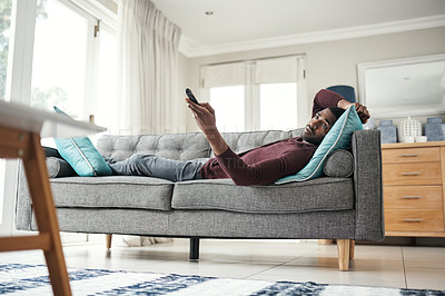 Buy stock photo Shot of a man using a remote control while lying on the couch at home