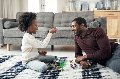 Buy stock photo Shot of a man sitting with his daughter while she plays with her toys at home