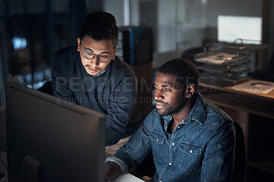 Buy stock photo Shot of two young businessmen using a computer during a late night in a modern office
