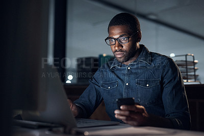 Buy stock photo Shot of a young businessman using a laptop and smartphone during a late night in a modern office