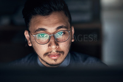 Buy stock photo Shot of a young businessman using a computer during a late night in a modern office