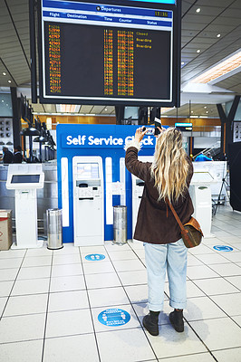 Buy stock photo Shot of a woman taking a photo of the time for her flight at the airport