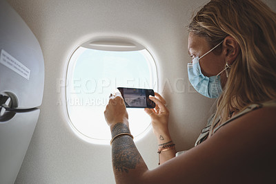 Buy stock photo Shot of  a young woman taking a photo of the view from her window seat in the aeroplane