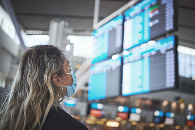 Buy stock photo Shot of a woman checking the time of her flight at the airport