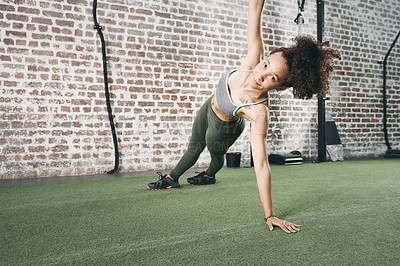 Buy stock photo Shot of a sporty young woman doing the side plank at the gym