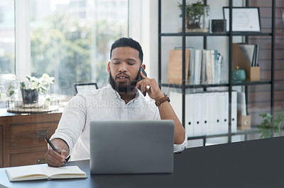 Buy stock photo Shot of a young businessman talking on a cellphone while writing notes and working on a laptop
