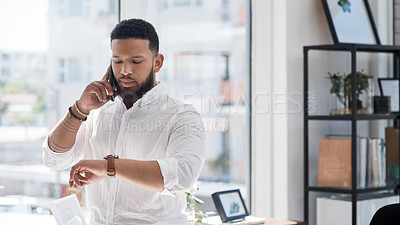Buy stock photo Shot of a young businessman checking the time on his wristwatch while talking on a cellphone in an office