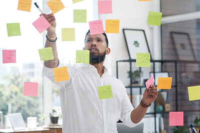Buy stock photo Shot of a young businessman brainstorming with sticky notes on a glass wall in an office