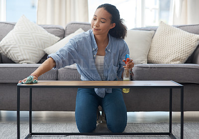 Buy stock photo Shot of a young woman cleaning down her wood coffee table at home