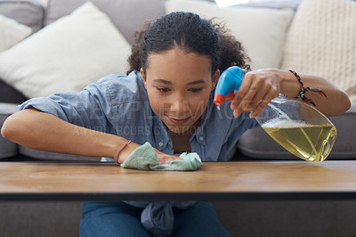 Buy stock photo Shot of a young woman wiping down her wooden coffee table in her living room at home