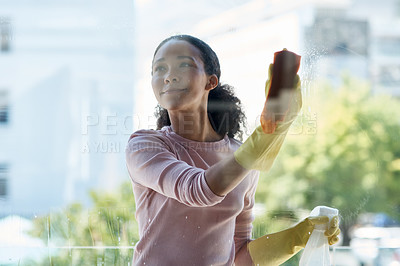 Buy stock photo Shot of a young woman cleaning her window at home