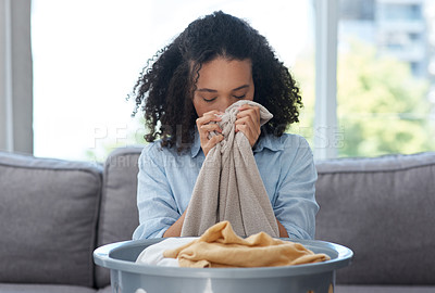 Buy stock photo Shot of a young woman smelling freshly cleaned laundry in satisfaction