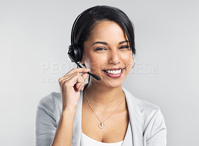 Buy stock photo Studio shot of a confident young businesswoman using a headset against a grey background