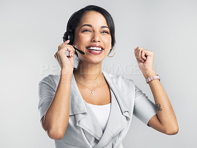 Buy stock photo Studio shot of a confident young businesswoman using a headset and cheering against a grey background
