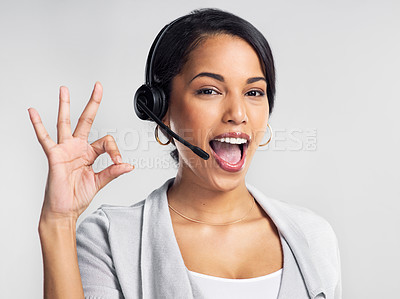 Buy stock photo Studio shot of a young businesswoman using a headset and showing an okay sign against a grey background