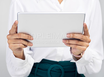 Buy stock photo Studio shot of an unrecognisable businesswoman using a digital tablet against a grey background
