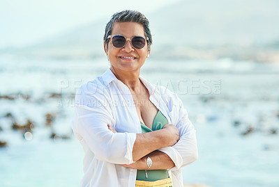 Buy stock photo Shot of an attractive mature woman standing alone with her arms folded during a day out on the beach