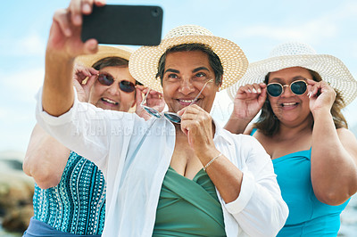 Buy stock photo Shot of a mature group of friends standing together and using a cellphone to take a selfie on the beach