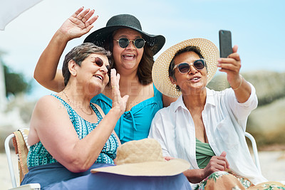 Buy stock photo Shot of a mature group of friends using a cellphone for a video chat during a day on the beach