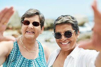 Buy stock photo Shot of two mature friends standing together and posing for a selfie during a day out on the beach