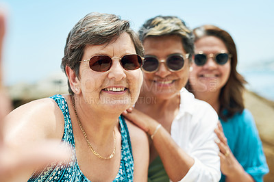 Buy stock photo Shot of a mature group of friends standing together and posing for a selfie during a day on the beach