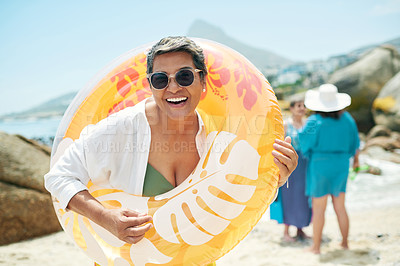 Buy stock photo Shot of a mature woman standing and holding a pool inflatable during a day on the beach with friends
