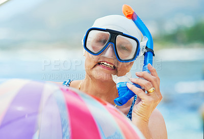 Buy stock photo Shot of a mature woman wearing snorkel gear and holding an inflatable ball during a day on the beach